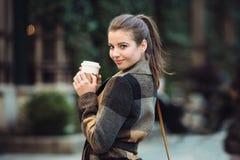拿着咖啡杯和走在城市街道上的美丽的女实业家到工作在春天 库存照片