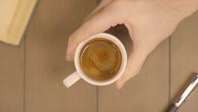 拿着咖啡杯早晨饮料的人的手 男性移动一杯咖啡 咖啡用在木的流动的牛奶 库存照片