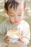 拿着咖啡杯的一个英俊的泰国男婴 免版税库存图片