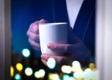 拿着咖啡杯的人由窗口 免版税库存图片