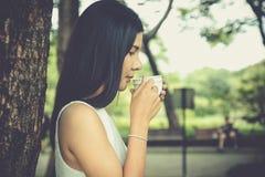 拿着咖啡杯的少妇在公园 库存照片
