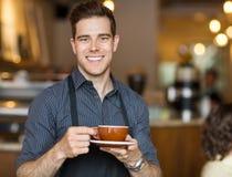 拿着咖啡杯的愉快的侍者在自助食堂 库存照片