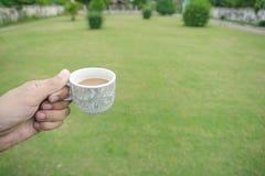 拿着咖啡杯的手 庭院背景 库存图片