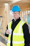 拿着咖啡杯的木匠在建造场所 库存照片