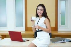 拿着咖啡杯的美丽的亚裔女商人在她的书桌 免版税库存照片