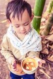 拿着咖啡杯的英俊的泰国男婴 库存照片