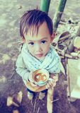 拿着咖啡杯的英俊的泰国男婴 免版税库存照片