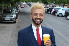 拿着咖啡杯的逗人喜爱的非洲的商人户外 免版税库存照片
