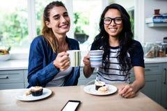 拿着咖啡杯的年轻女性朋友在早餐期间 库存照片