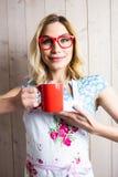 拿着咖啡杯的围裙的微笑的妇女反对纹理背景 库存图片
