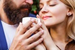 拿着咖啡的女性和人手 结合在握手用咖啡的爱 享受coffe的夫妇 ?? 免版税库存照片