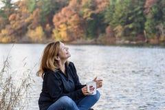 拿着咖啡的妇女笑沿有colorf的湖边平地 免版税库存照片