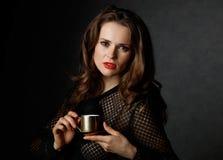 拿着咖啡的妇女画象反对黑暗的背景 免版税库存照片