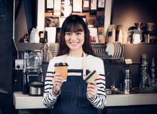 拿着咖啡的妇女barista去杯子和信用卡,亚洲fema 免版税库存照片