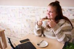 拿着咖啡的年轻成人胖的妇女,当微笑时 免版税库存图片