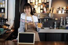 拿着咖啡的微笑的亚洲barista在咖啡的柜台 库存照片