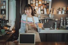 拿着咖啡的微笑的亚洲barista在逆酒吧与 免版税库存照片