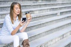 拿着咖啡的快乐的时髦的女人户外 免版税库存照片