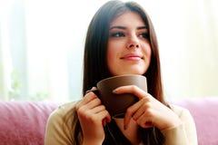 拿着咖啡的愉快的体贴的妇女 库存照片