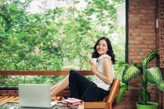 拿着咖啡的聪明的便衣的确信的年轻亚裔妇女 库存照片