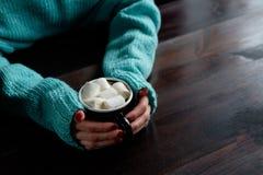 拿着咖啡的蓝色毛线衣的女孩用蛋白软糖韩 免版税库存图片