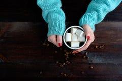拿着咖啡的蓝色毛线衣的女孩用蛋白软糖韩 库存图片