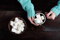 拿着咖啡的蓝色毛线衣的女孩用蛋白软糖韩 库存照片