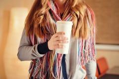 拿着咖啡的翻转者在咖啡馆的少妇 免版税库存照片