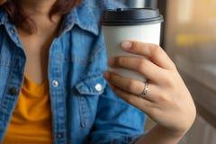 拿着咖啡纸杯的手 库存照片