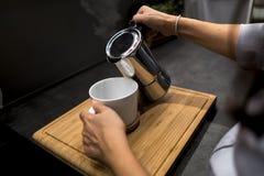 拿着咖啡罐倾吐的咖啡的妇女入白色杯子 免版税库存图片
