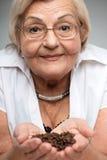 拿着咖啡豆的年长妇女 免版税库存照片