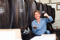拿着品尝的人酿酒商葡萄酒杯 免版税库存照片
