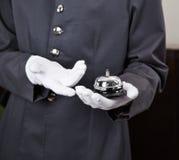 拿着响铃的服务生在旅馆里 库存照片