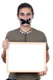 拿着哑海报的男孩 免版税库存图片