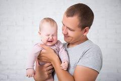 拿着哭泣的女婴的年轻父亲画象 免版税库存照片