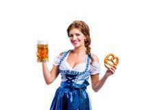 拿着啤酒和椒盐脆饼的传统巴法力亚礼服的妇女 免版税库存图片