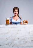 拿着啤酒和椒盐脆饼的传统巴法力亚礼服的妇女 免版税图库摄影