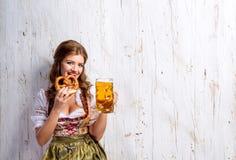 拿着啤酒和椒盐脆饼的传统巴法力亚礼服的妇女 免版税库存照片