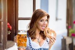 拿着啤酒和椒盐脆饼的传统巴法力亚礼服的妇女 图库摄影