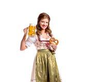 拿着啤酒和椒盐脆饼的传统巴法力亚礼服的妇女 库存图片