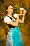 拿着啤酒大啤酒杯的年轻巴法力亚妇女 库存照片