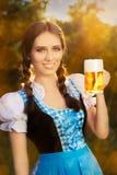 拿着啤酒大啤酒杯的年轻巴法力亚妇女 免版税库存照片