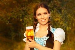 拿着啤酒大啤酒杯的年轻巴法力亚妇女 免版税库存图片