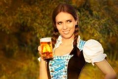 拿着啤酒大啤酒杯的年轻巴法力亚妇女 库存图片