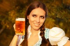 拿着啤酒大啤酒杯的年轻巴法力亚妇女 图库摄影