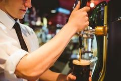 拿着啤酒杯的侍酒者在分配器轻拍下 免版税库存照片
