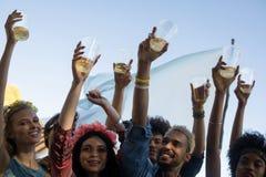 拿着啤酒杯的愉快的朋友,当享受音乐节时 免版税库存照片