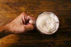 拿着啤酒杯的手有很多冷的新酒精饮料 图库摄影