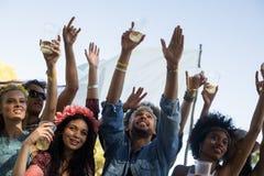 拿着啤酒杯的朋友,当享受音乐节时 图库摄影