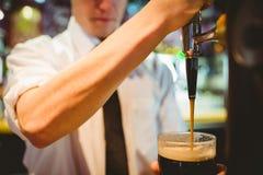 拿着啤酒杯的酒吧老板在分配器轻拍下 免版税库存图片